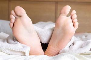 Female, Feet, Sticking, Out, Of, Blanket, On, Bed, Stock, Photo