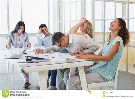 dim up au bureau casual business team laughing during meeting stock image
